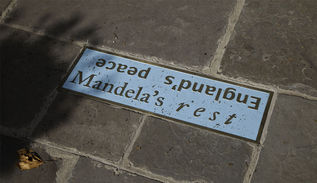 A cast iron enamelled plaque set into a stone footpath